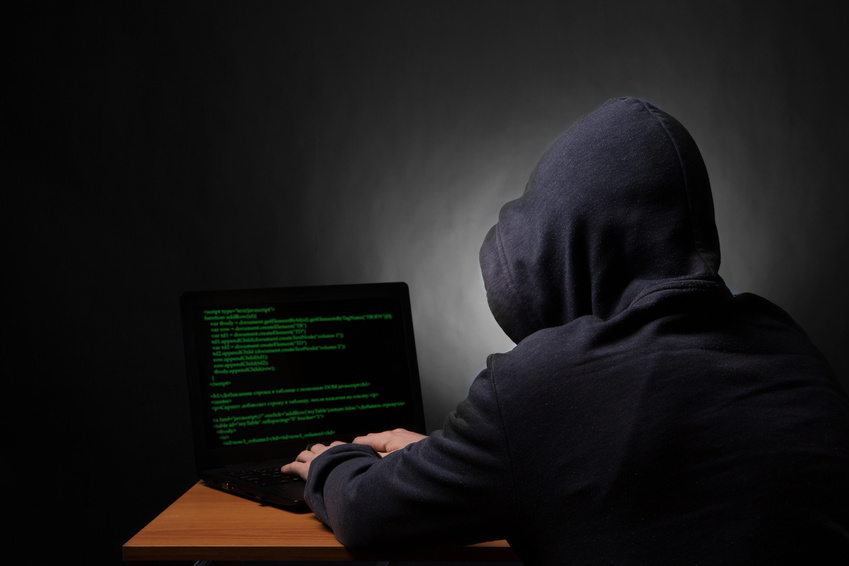 Hacker in hood with laptop initiating cyber attack.